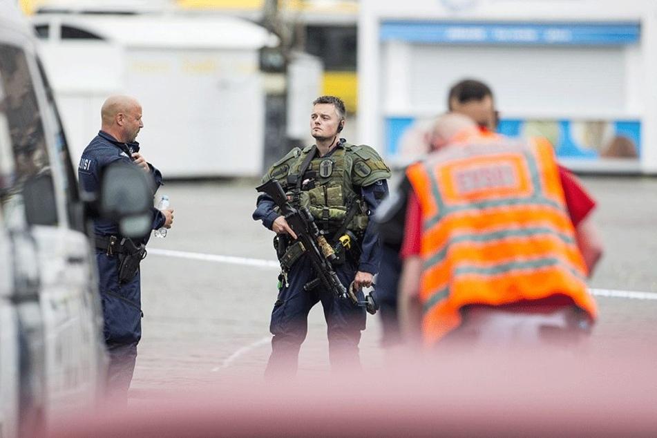 Ein schwer bewaffneter Polizist steht auf dem Marktplatz in Turku.