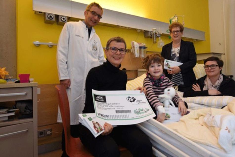 AOK Plus-Sprecherin Hannelore Strobel (vorn) bringt der kleinen Melissa Hille (5) Theaterkarten ans Krankenbett.