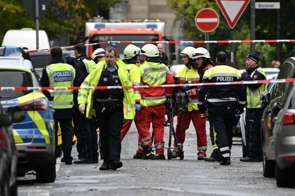 Sanitäter bringen einen Mann zum Krankenwagen der aus einem Fenster gesprungen ist.