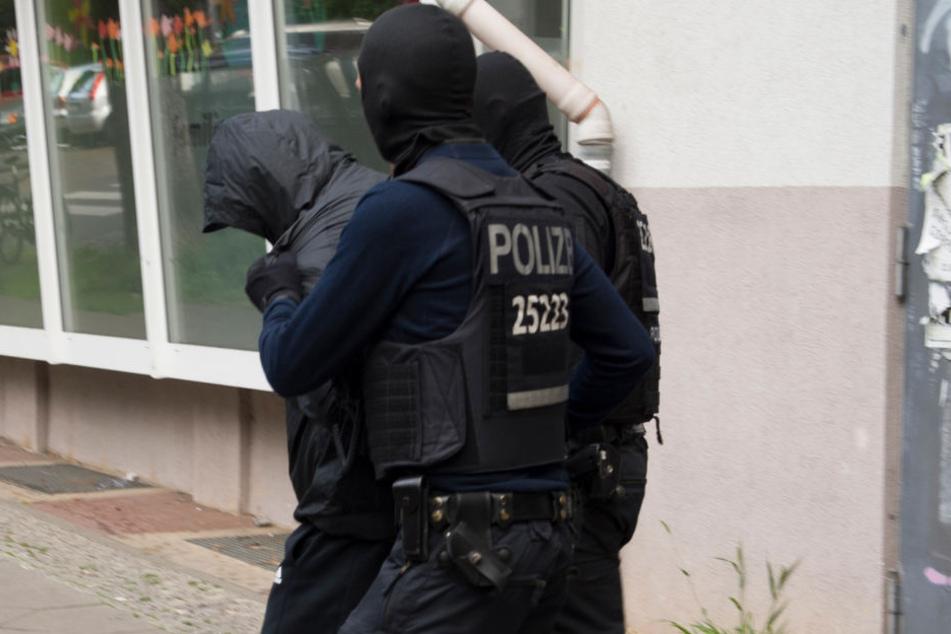 Berliner Polizisten führen einen Verdächtigen ab. (Symbolbild)