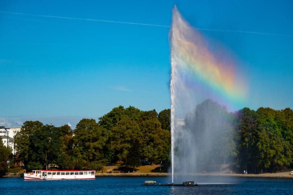 Ein Regenbogen entsteht durch die Sonnenstrahlen in der Alsterfontäne, die gerade von einem Alsterausflugsdampfer passiert wird.