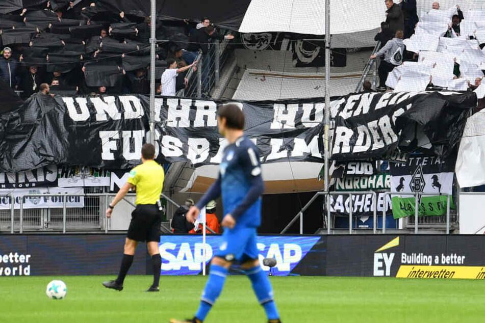 """Beim Spiel 1899 Hoffenheim - Borussia Mönchengladbach am Samstag hielten Gladbacher Fans zu Spielbeginn einen Spruchband mit der Aufschrift """"Und ihr? Huren eines Fussballmörders""""! hoch."""