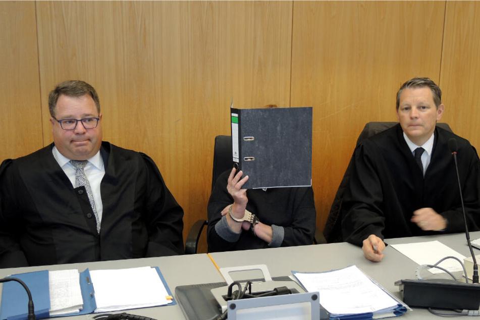 Ulm: Die Angeklagte (M) in einem Prozess wegen Vergewaltigung von zwei demenzkranken Frauen hält sich vor dem Beginn der Verhandlung in einem Saal im Landgericht einen Aktendeckel vor ihr Gesicht.