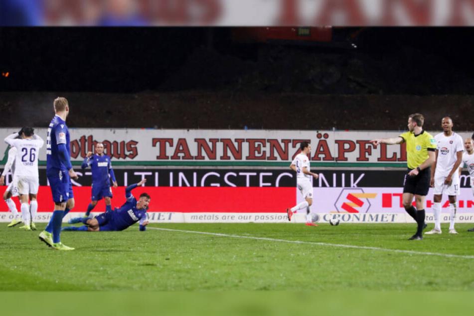 Sören Gonther (Nummer 26) schlägt die Hände vors Gesicht, während Schiedsrichter Sven Waschitzki nach dem vermeintlichen Foul auf den Elfmeterpunkt zeigt.