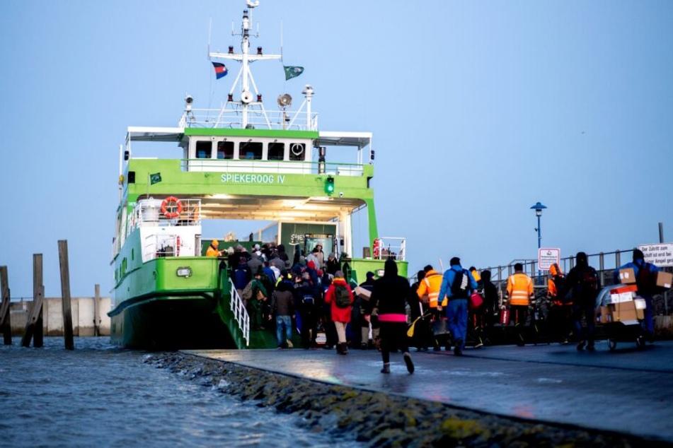"""Neuharlingersiel: Fahrgäste betreten die Fähre """"Spiekeroog IV"""", die bei hohem Wasserstand im Hafen liegt."""