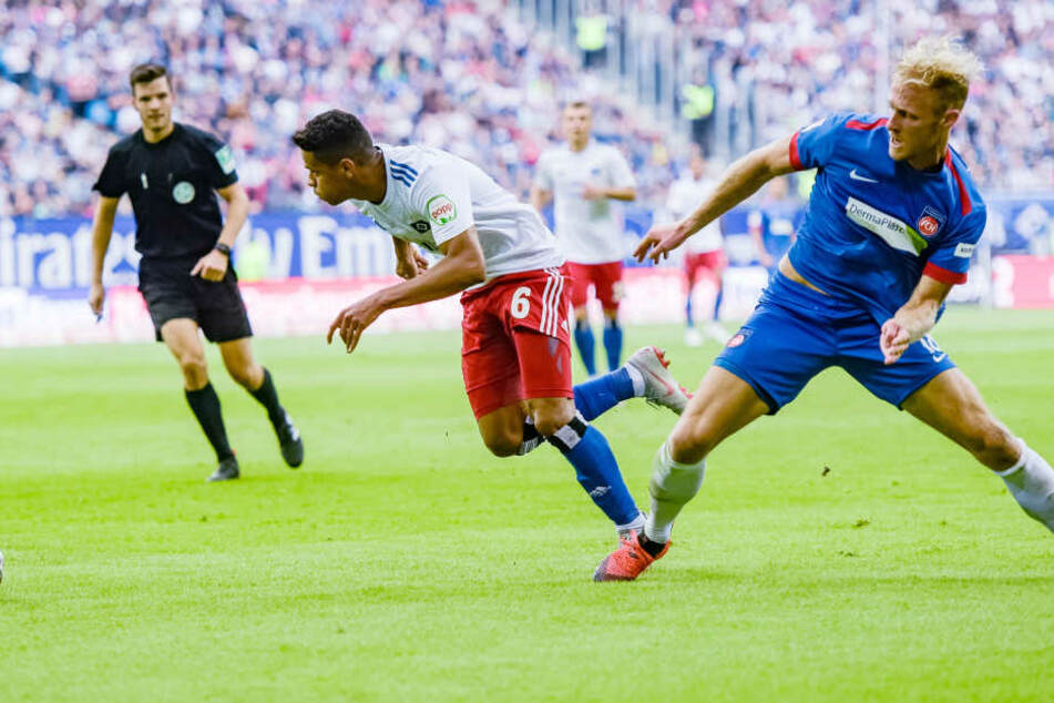 Hamburgs Douglas Santos (M) setzt sich gegen Heidenheims Sebastian Griesbeck (r) durch.