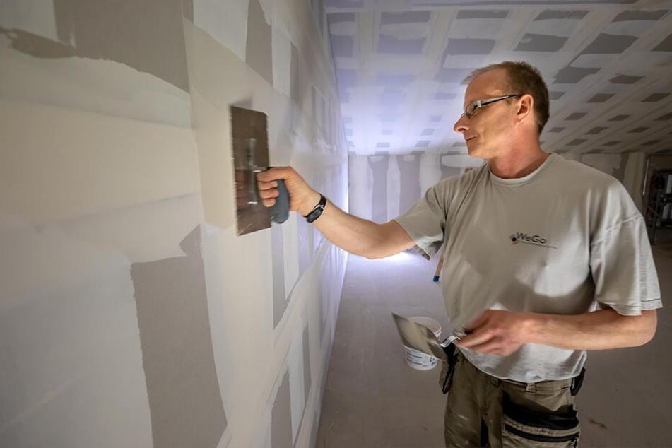 Trockenbauer Ralf Mehner (47) verspachtelt eine Wand in künftigen Lagerräumen.