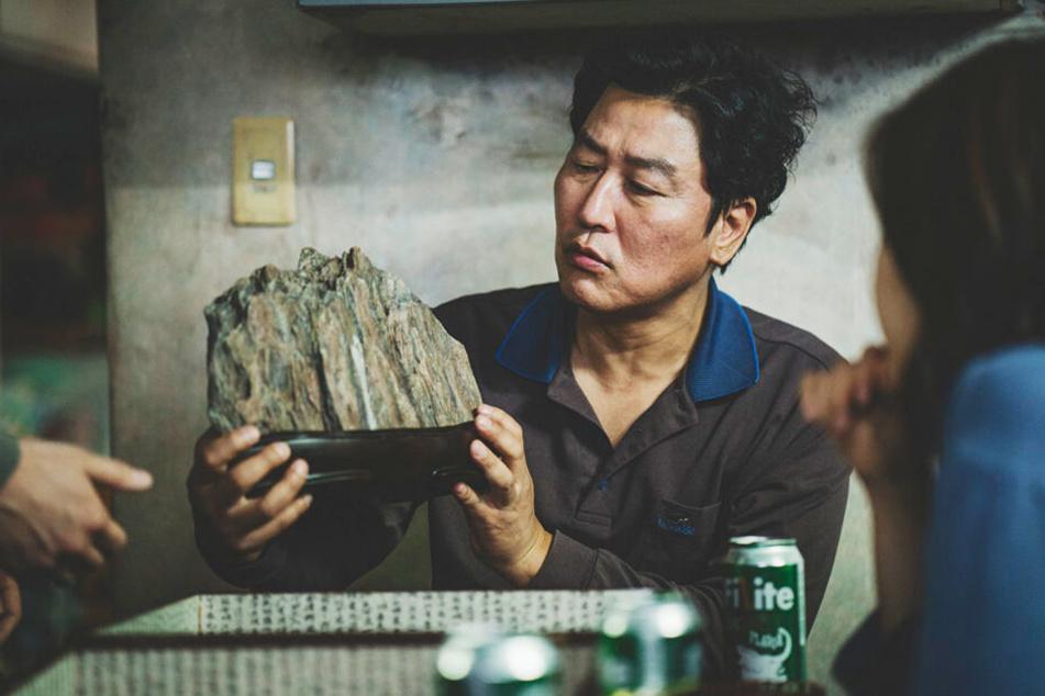 Kim Ki-taek (Kang-ho Song) betrachtet einen schönen Stein.