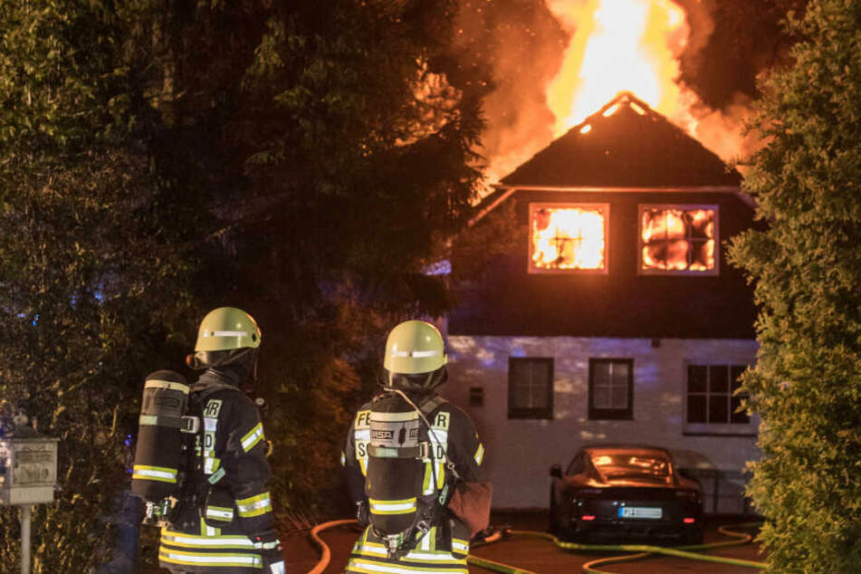 Feuerwehrleute stehen vor dem brennenden Haus.
