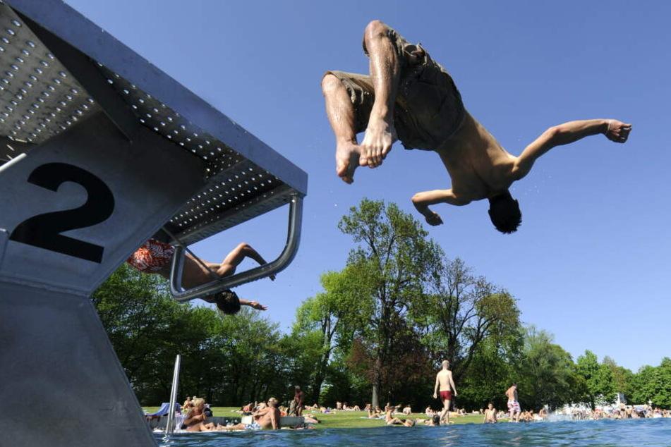 Ein junger Mann springt am Freitag in München im Schyrenbad in das Becken. Das Freibad eröffnet im Mai die Badesaison. (Archivbild)