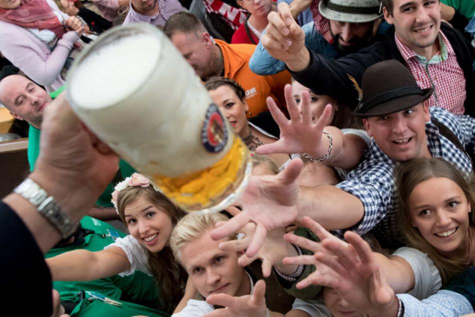 Besucher freuen sich beim Auftakt zum Oktoberfest 2017 über ihr erstes Bier.