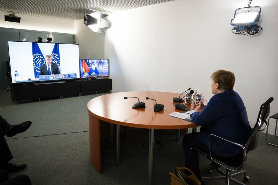 Bundeskanzlerin Angela Merkel nimmt an einer Videokonferenz mit den Vorsitzenden von internationaler Wirtschafts- und Finanzorganisationen ILO, IWF, OECD, Weltbank und WTO im Bundeskanzleramt teil. (auf dem Monitor ist Guy Ryder, Generaldirektor der Internationalen Arbeitsorganisation ILO zu sehen).