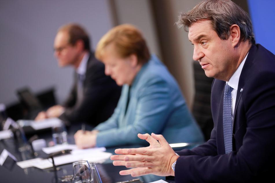 Markus Söder (r-l), Ministerpräsident von Bayern und Vorsitzender der CSU, spricht neben Bundeskanzlerin Angela Merkel (CDU) und Michael Müller (SPD), Regierender Bürgermeister von Berlin, auf einer Pressekonferenz.