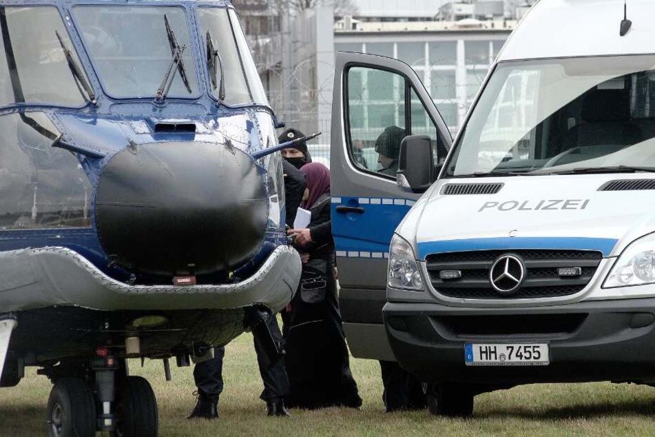 Die Frau wird am Flughafen Hamburg von einem Gefangenentransporter in einen Hubschrauber der Bundespolizei geführt.