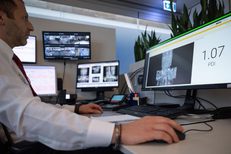Ein Mitarbeiter sitzt am Flughafen Stuttgart in einem Kontrollraum vor einem Computer, auf dem die Ergebnisse von Überwachungssensoren anzeigt.