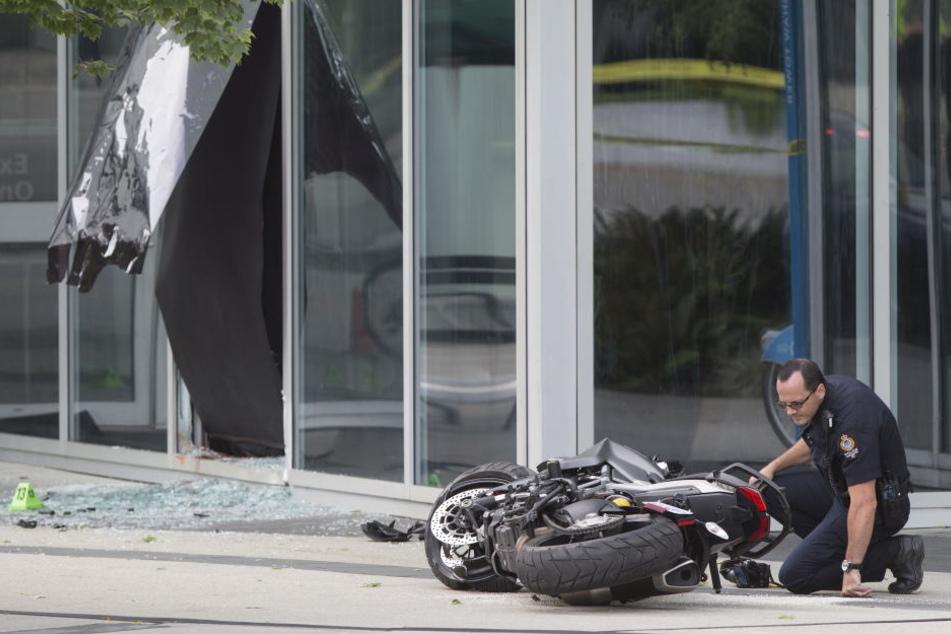 Ein Polizist untersucht das Motorrad der Stuntfrau.