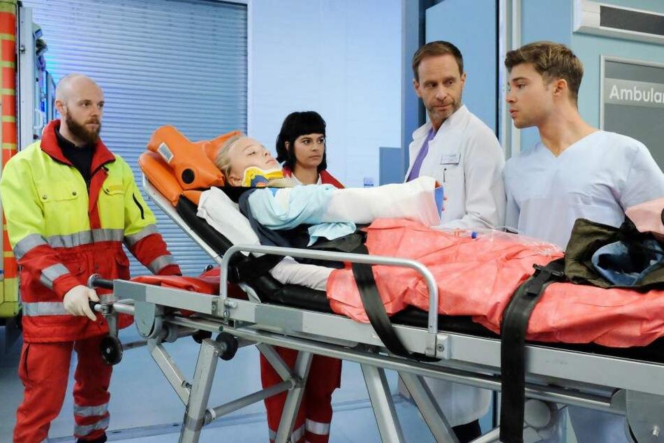 Laura Schütz wird mit einem gebrochenen Arm in die Sachsenklinik eingeliefert. Pfleger Kris Haas (r.) erkennt sofort die ehemalige Patientin von Dr. Philipp Brentano wieder.