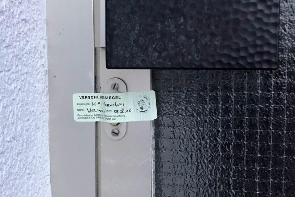 Ein Siegel der Polizei klebt an der Eingangstüre zu einem Wohnhaus. Die Polizei hat dort in der Nacht eine tote Frau und einen schwer verletzten Mann gefunden.