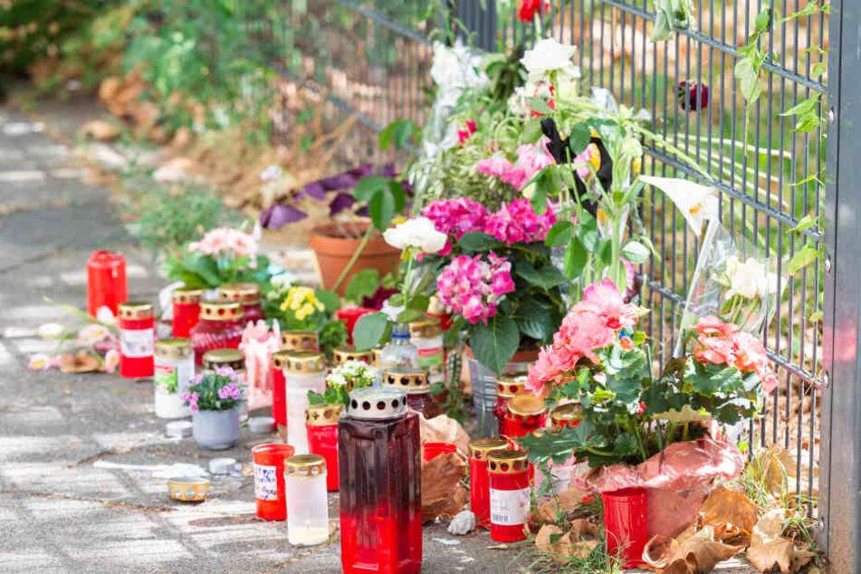 Am Tatort, an dem eine 36-jährige Frau erstochen wurde, liegen Blumen und Kerzen (Archivbild).
