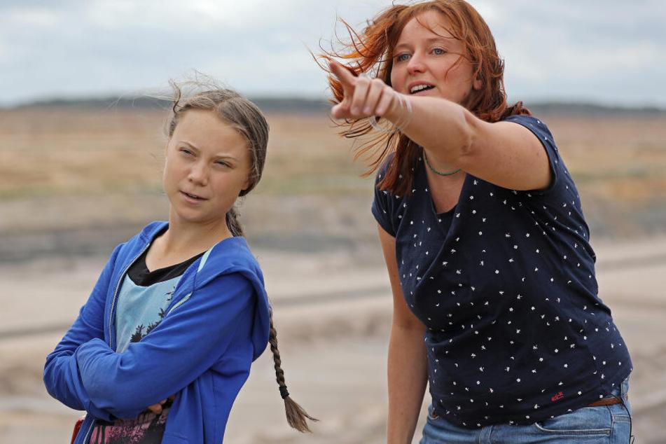 """Greta Thunberg (l), Klimaschutzaktivistin, steht mit Kathrin Henneberger, der Vertreterin des Aktionsbündnisses """"Ende Gelände"""", am Tagebau Hambach."""