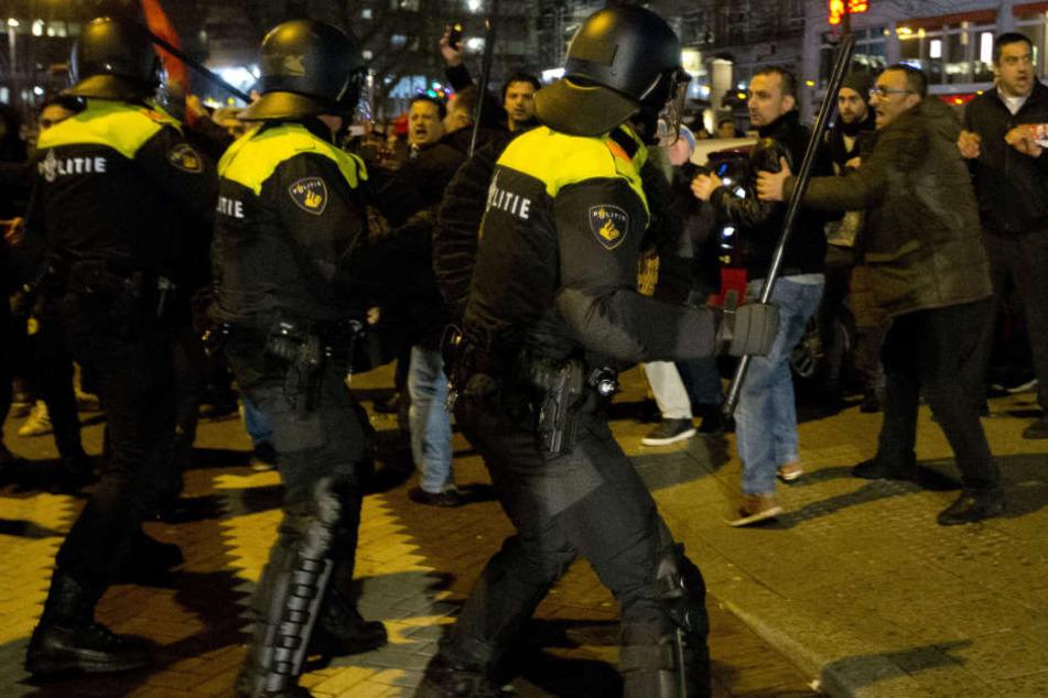 Polizeieinheiten stehen am türkischen Konsulat in Rotterdam Demonstranten gegenüber.