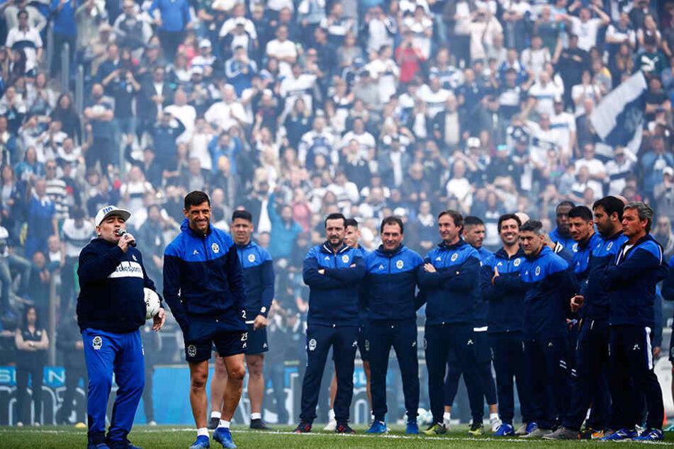 Irre Kulisse. Maradona mit seinem Team auf dem Platz vor der jubelnden Menge.