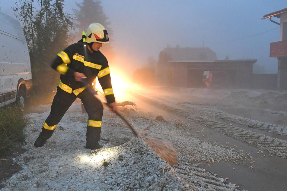 Feuerwehrleute räumen Hagel zur Seite. In Österreich haben Unwetter mit großen Hagelkörnern zahlreiche Gebäude und Autos beschädigt.