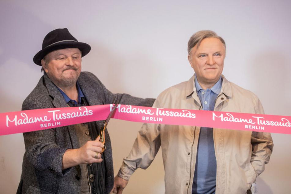 Axel Prahl schneidet ein rotes Band von Madame Tussauds durch.