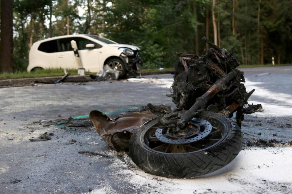 Ein verbranntes Motorrad liegt neben einem zerstörten Fahrzeug auf der L1147.