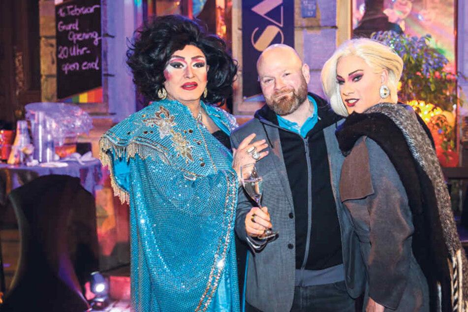 Barchef Ralf Liebscher freut sich über den Besuch der Drag-Queens Tess Tiger (l.) und Mel Kim (r.).