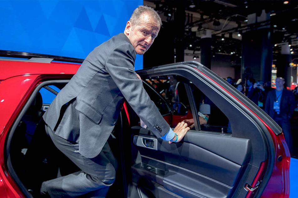 Herbert Diess (60), VW-Chef, steigt auf einer Messe aus einem Fahrzeug.