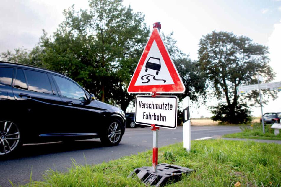 Schilder weisen Autofahrer auf eine wegen der Wollhandkrabben verschmutzten Fahrbahn hin.