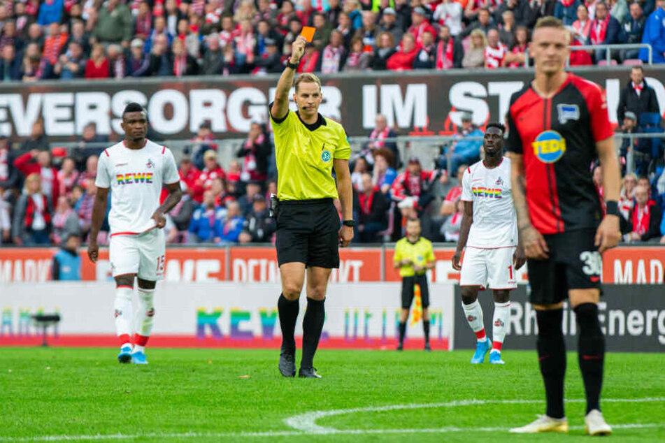 Schiedsrichter Sören Storks (M) zeigt nach Ansicht der Videobilder J. Meré (Nicht im Bild) von Köln die rote Karte.