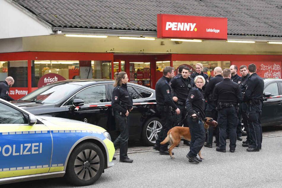 Polizeibeamte stehen vor dem Supermarkt in Lohbrügge.