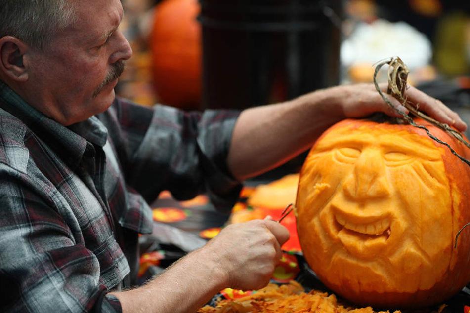 Ein Teilnehmer schnitzt dem Kürbis ein gruseliges Gesicht.