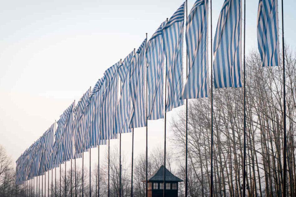 Über den Wachtürmen des früheren Konzentrationslagers Auschwitz-Birkenau wehen Fahnen im Stil der blau-weiß gestreiften KZ-Häftlingskleidung im Wind.