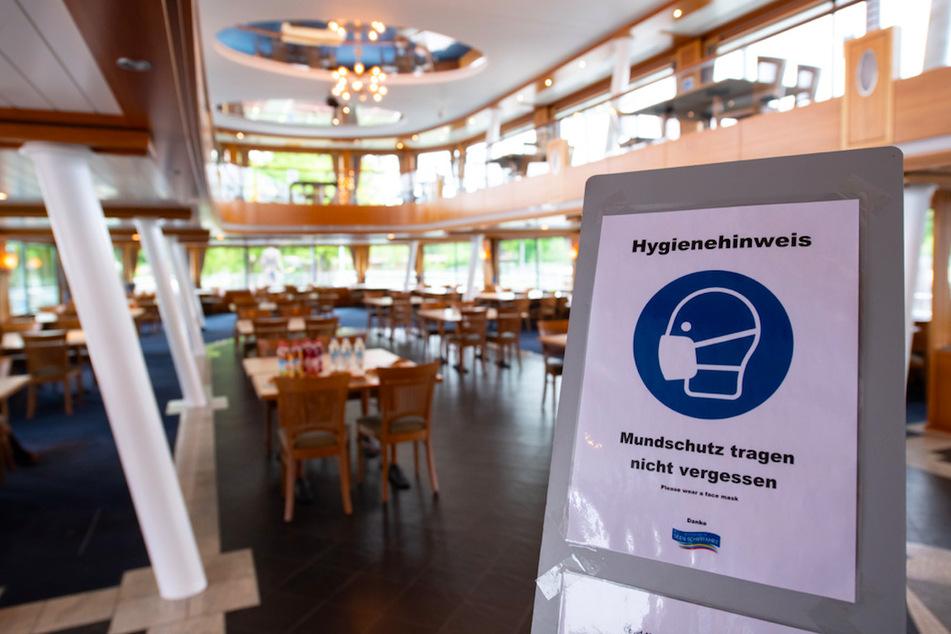 """Ein Schild mit der Aufschrift """"Hygienehinweis - Mundschutz tragen nicht vergessen"""" ist im Eingangsbereich der MS Starnberg am Starnberger See aufgestellt."""