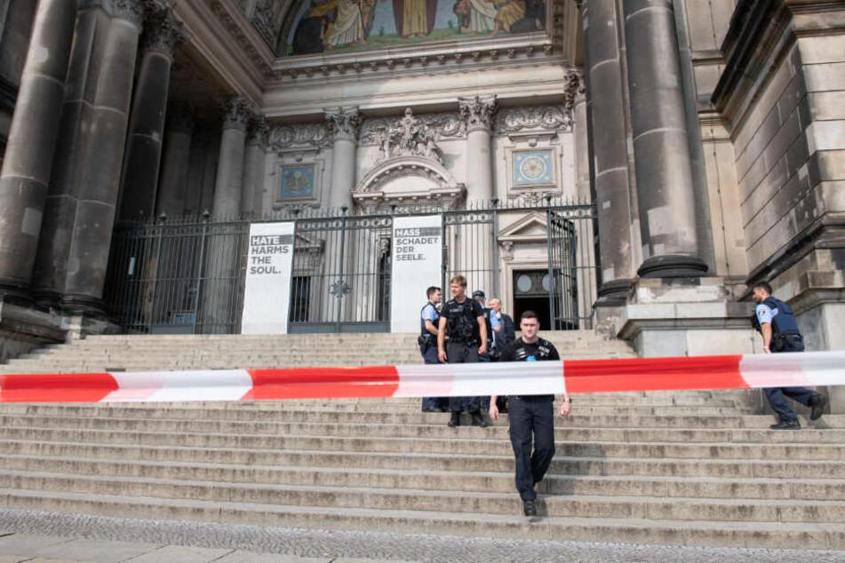 Polizisten stehen auf der Treppe des Eingangs zum Berliner Dom.