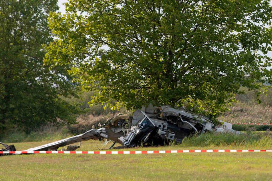 er Wrack eines Kleinflugzeugs liegt nach einem Absturz auf einem Feld zwischen dem Ortsteil Badingen und Gransee hinter einem Absperrband der Polizei.