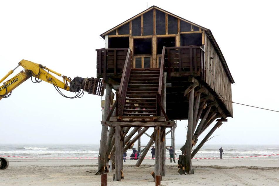 Ein Pfahlbau wird am Strand von St.Peter-Ording abgerissen. Der Bau mit Toiletten und Umkleideräumen wird durch einen Neubau ersetzt, der 100 Meter weiter ins Landesinnere gebaut wird.