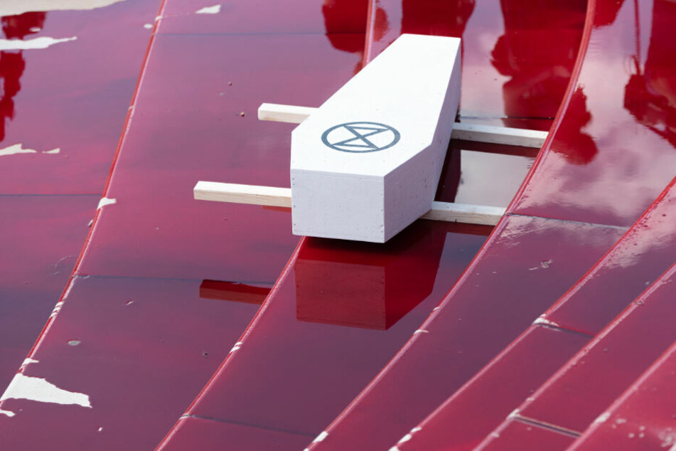 Die Klimaschützer haben einen Sarg mit dem Symbol der Gruppierung Extinction Rebellion einer blutroten Flüssigkeit am Hamburger Hafen abgestellt.
