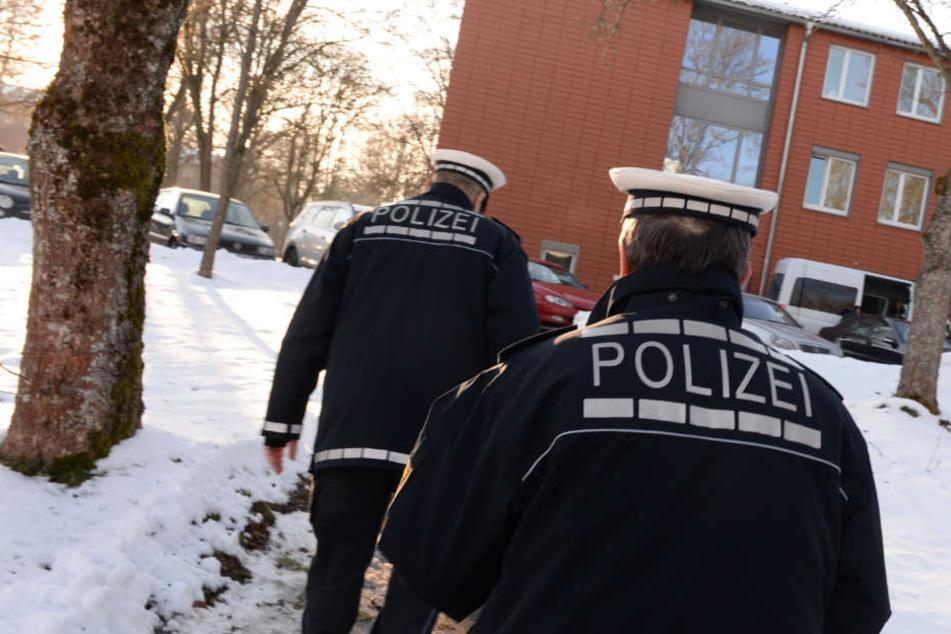 Zwei Polizisten gehen in der ehemaligen Kaserne zu einer Unterkunft, in der neue Asylbewerber untergebracht sind. (Archivbild)