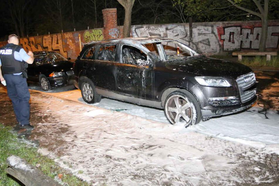 Ein Polizist begutachtet das abgebrannte Fahrzeug.