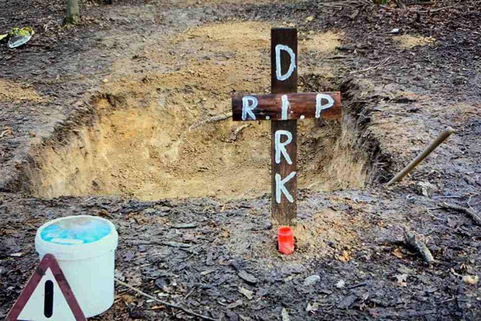 """Dieses im Januar aufgenommene und von der Polizei zur Verfügung gestellte Foto zeigt eine Grube mitten im Hambacher Forst, davor ein Kreuz mit der Inschrift """"R.I.P. Dirk""""."""