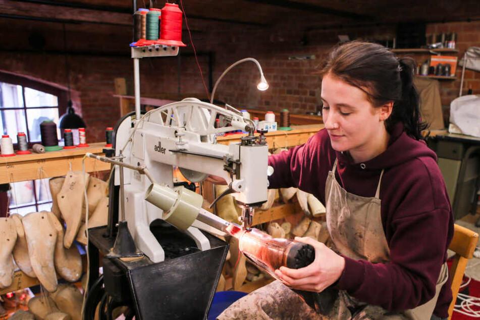 An einer besonders robusten Nähmaschine fügt Eva Lederteile und Sohle zum Schuh zusammen.