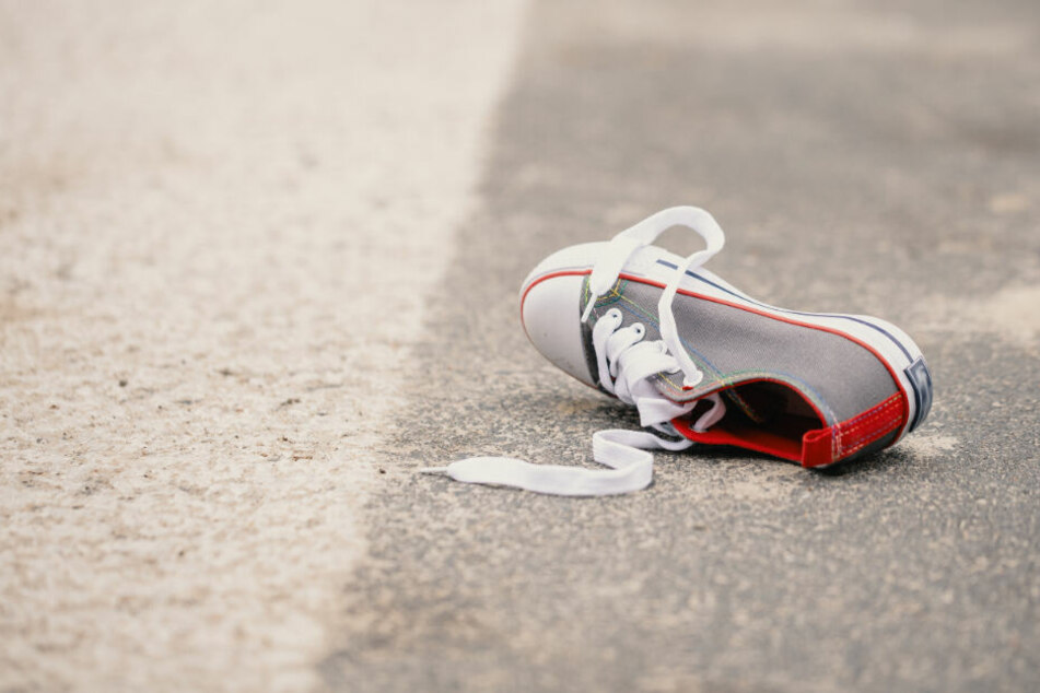 Der Schuh eines Kindes liegt auf der Straße. (Symbolfoto)