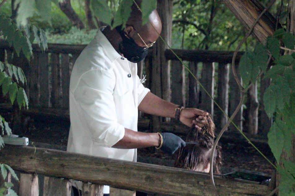 Herman James schneidet mit Mundschutz und Schutzhandschuhen einer Kundin im New Yorker Central Park die Haare.