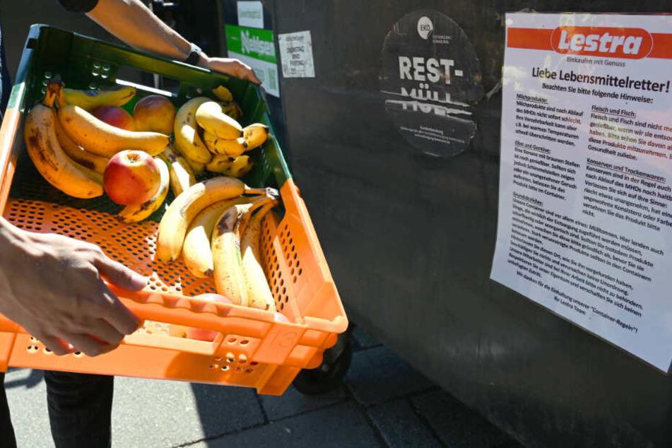 Eine Kiste voll mit Obst landet in einer Mülltonne.