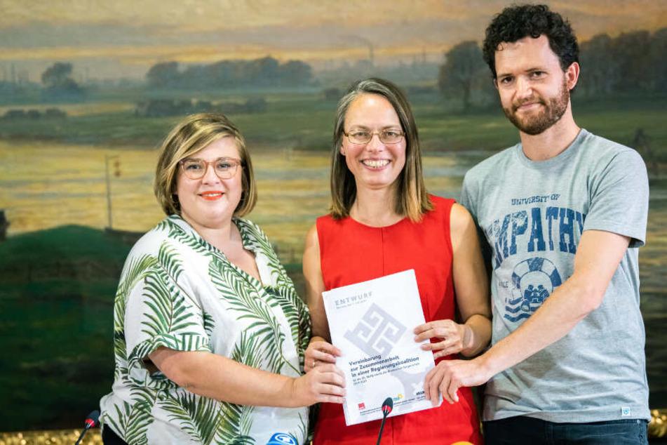 Alexandra Werwath (Grüne), Sascha Karolin Aulepp (SPD) und Felix Pithan (Linke) halten den Entwurf des Koalitionsvertrages in ihren Händen.