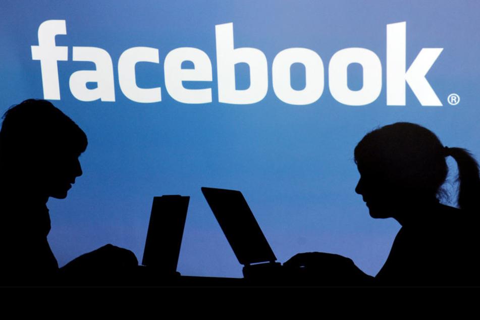Die Schatten von Jugendlichen mit einem Laptop vor dem Schriftzug des sozialen Internet-Netzwerks Facebook.